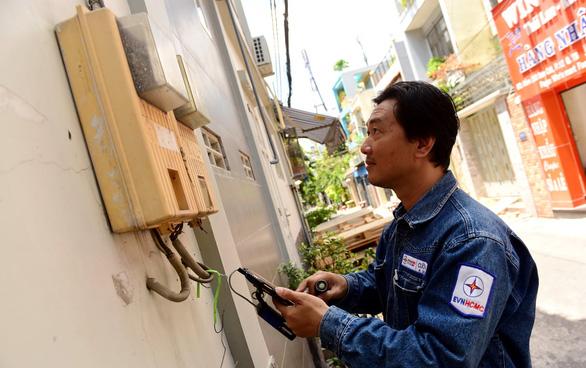 Nhân viên Công ty điện lực Tân Bình, TP.HCM Nguyễn Chí Cường ghi số điện trên đường Bàu Cát, Q. Tân Bình, TP.HCM trưa 22-4 - Ảnh: QUANG ĐỊNH